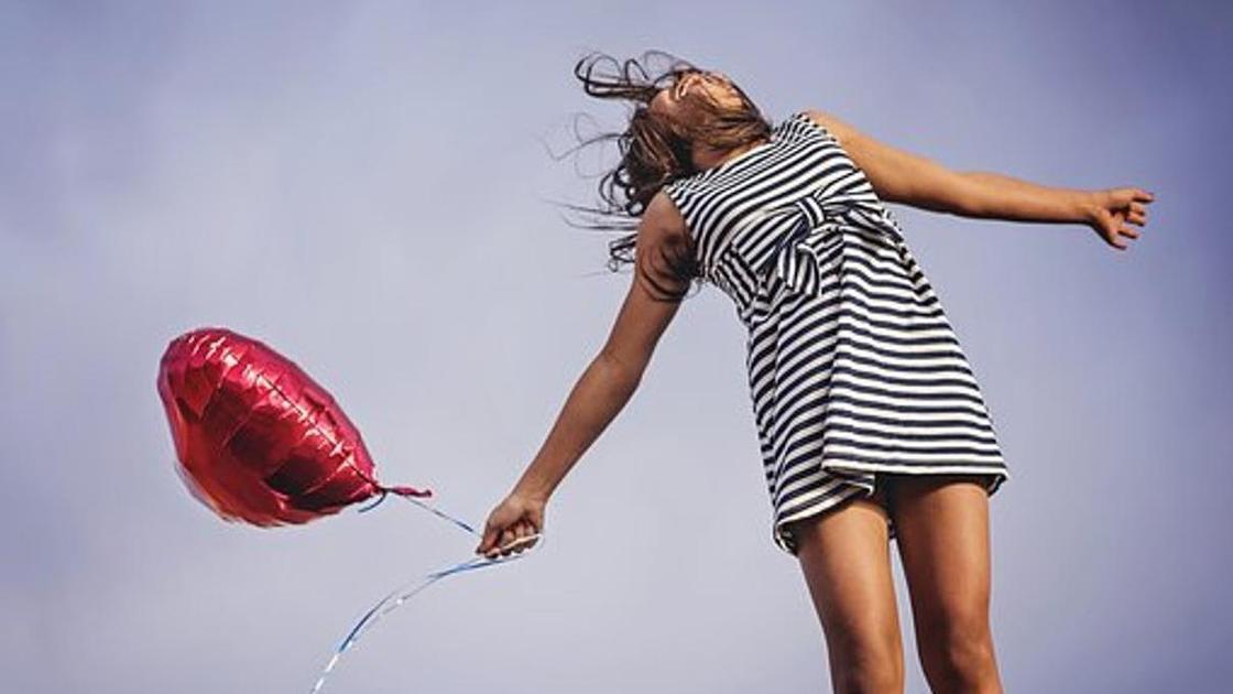 Девушка в полосатом платье с шаром в форме сердца