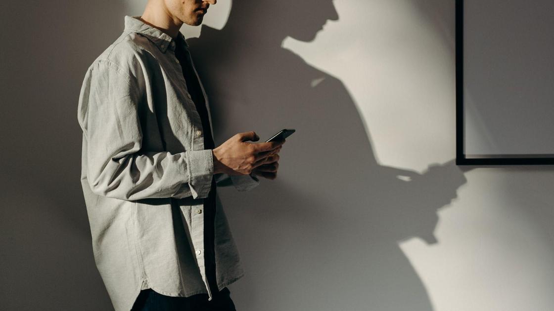 Мужчина держит в руках телефон