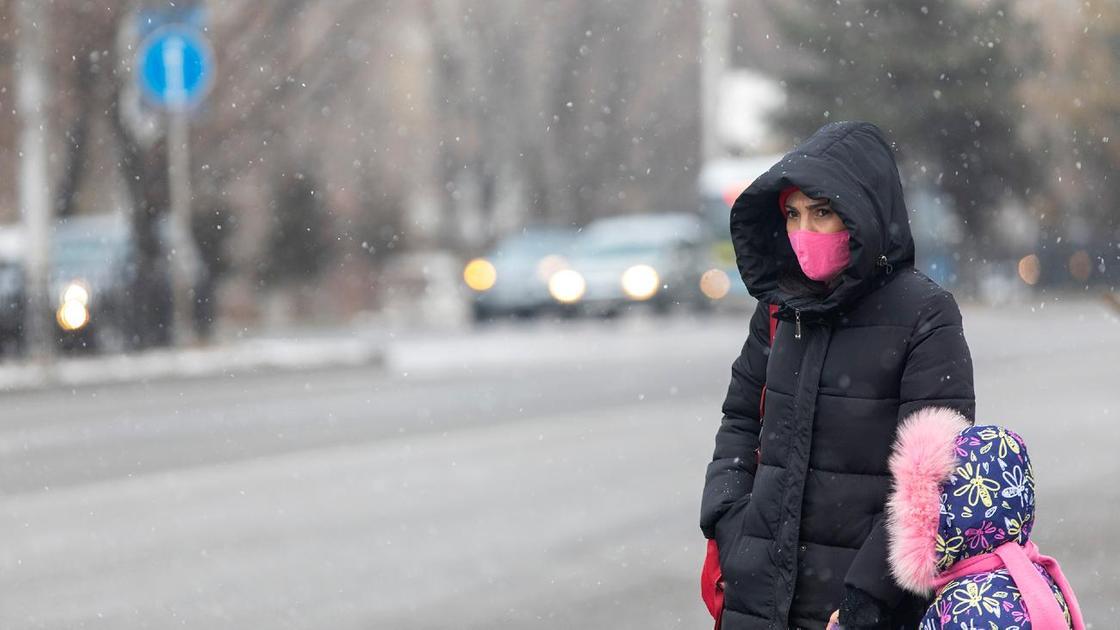 Женщина с ребенком стоят около проезжей части