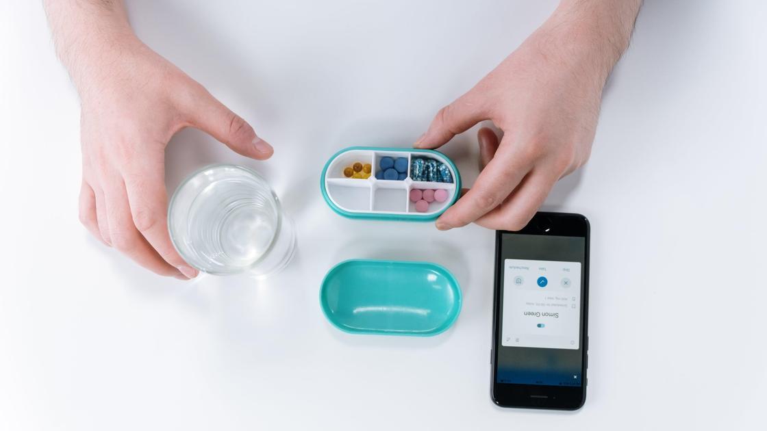 Таблетки на столе со стаканом воды