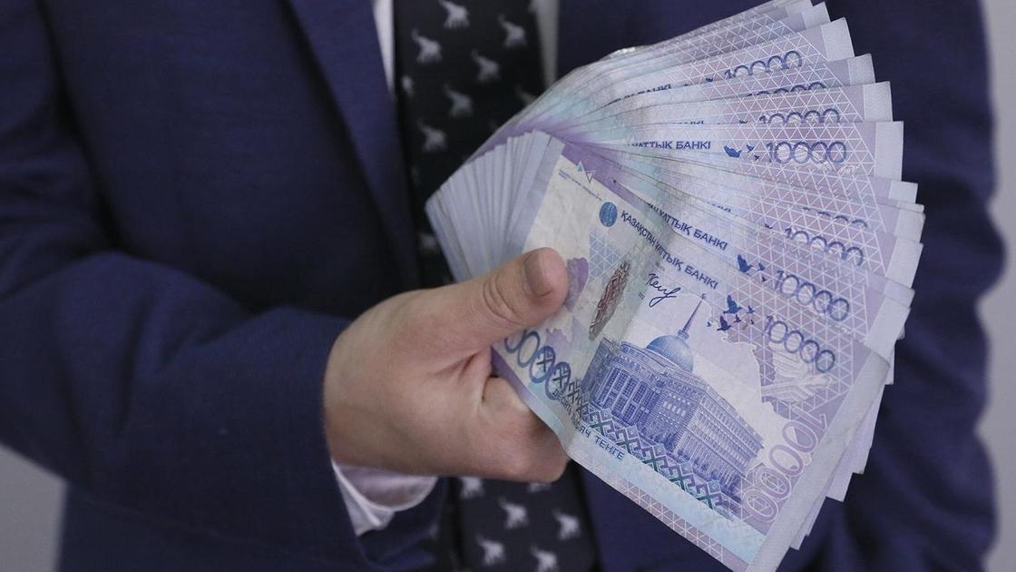 Мужчина держит деньги веером в руках