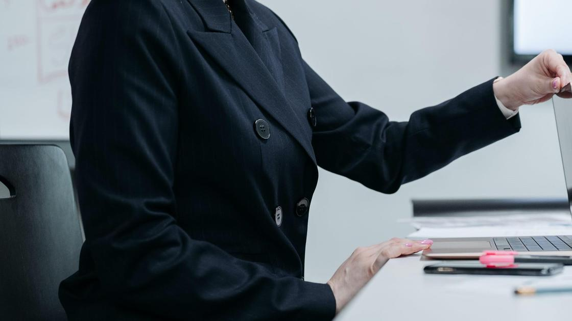 Женщина в костюме сидит за ноутбуком