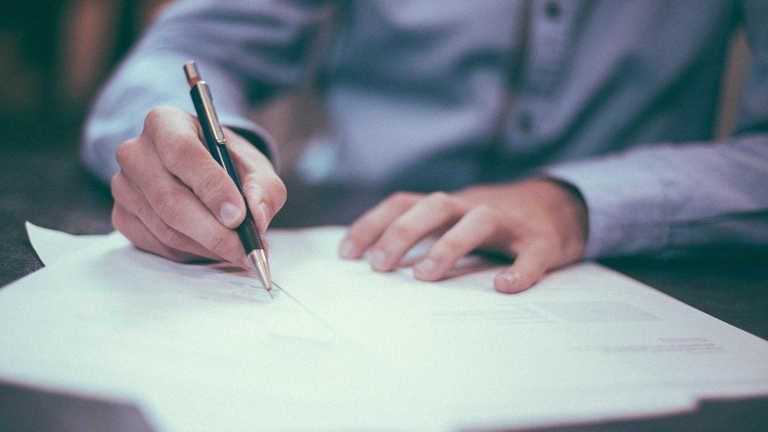 Мужчина подписывает документы
