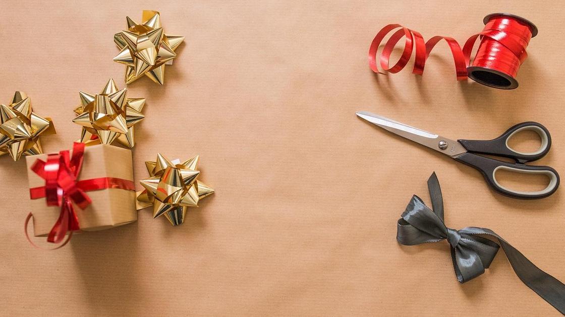 Упакованный подарок, ножницы, украшения из ленточек