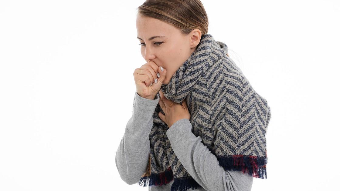 Женщина кашляет и прикрывает кулаком рот