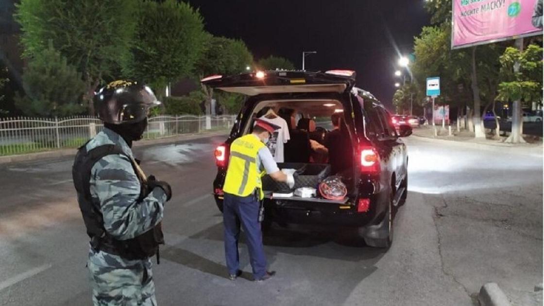 боец спецназа и полицейский проверяют машину