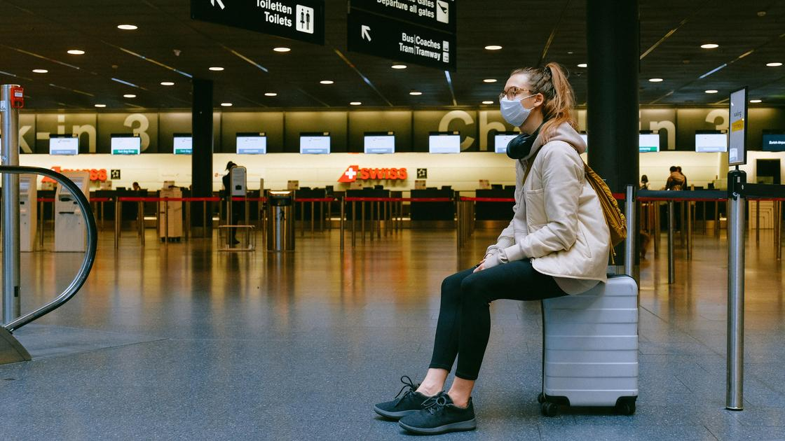Девушка сидит на чемодане в аэропорту