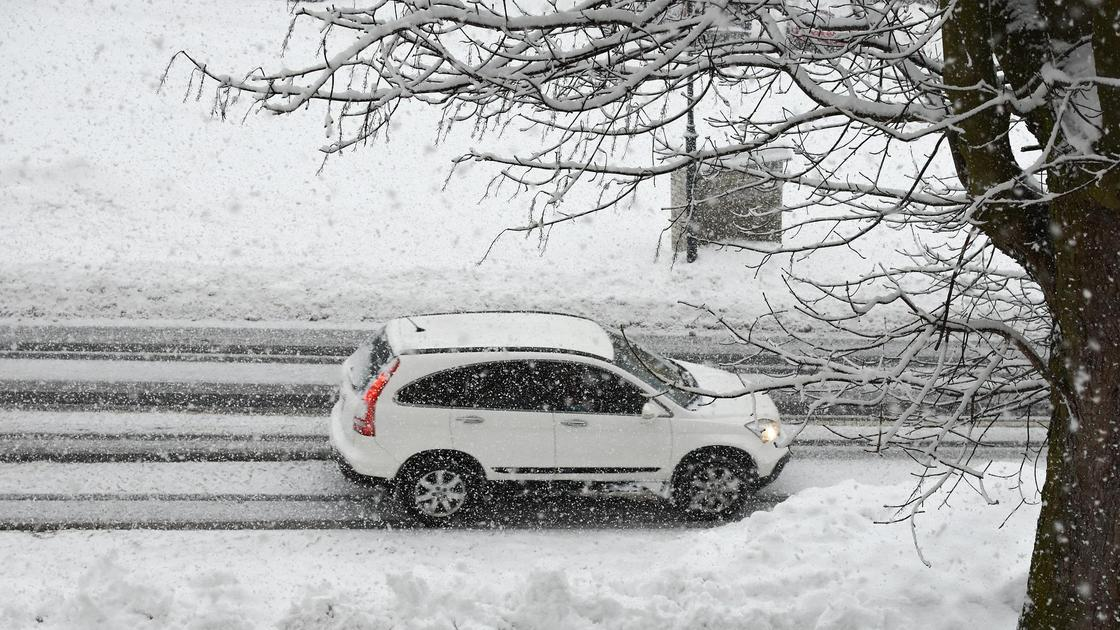 машина стоит под деревом на снегу