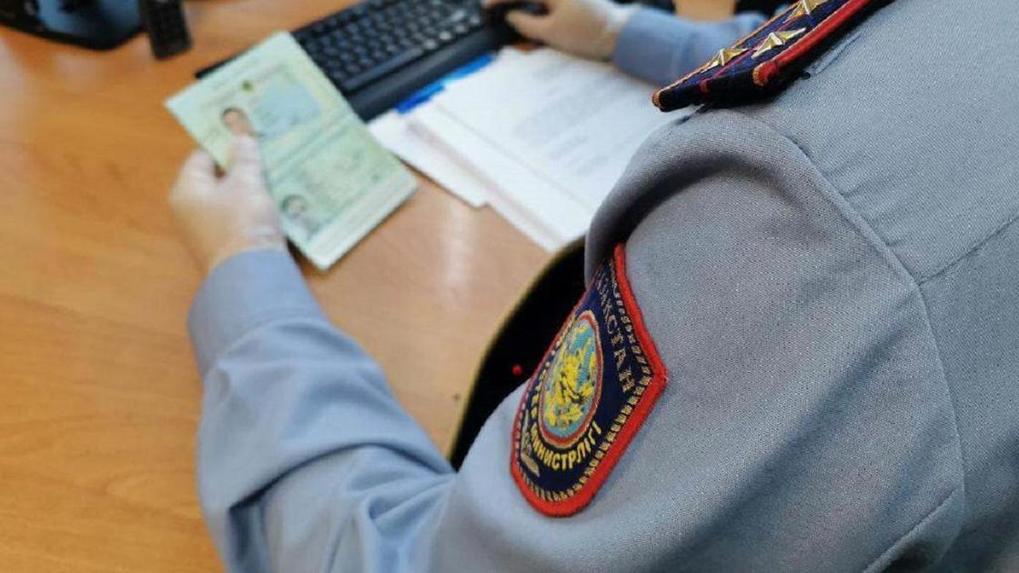 Полицейский проверяет данные в паспорте