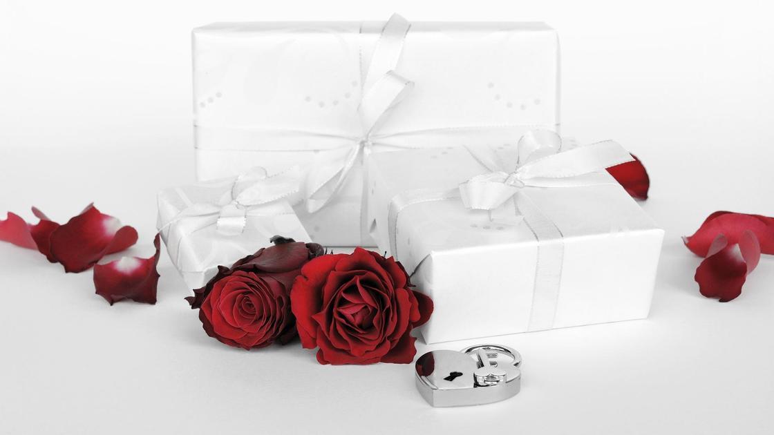 Упакованные подарки, розы и лепестки роз