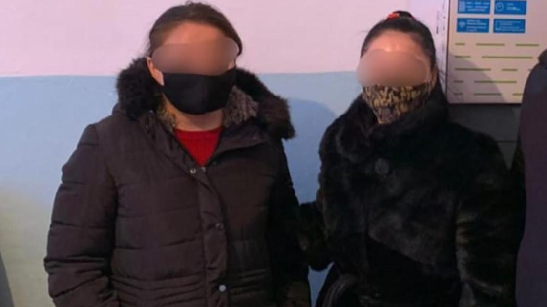 Две женщины в масках и верхней одежде стоят рядом друг с другом