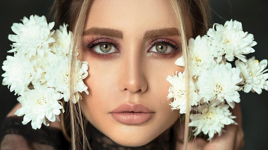 Девушка с накрашенными ресницами держит возле головы белые хризантемы