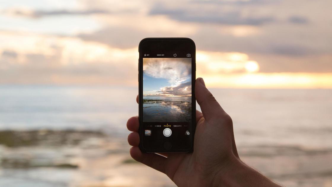 Человек фотографирует закат на смартфон