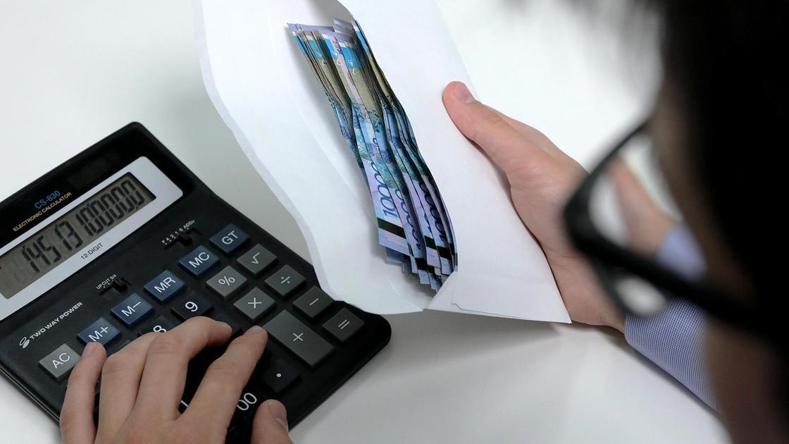 Мужчина держит в руках конверт денег