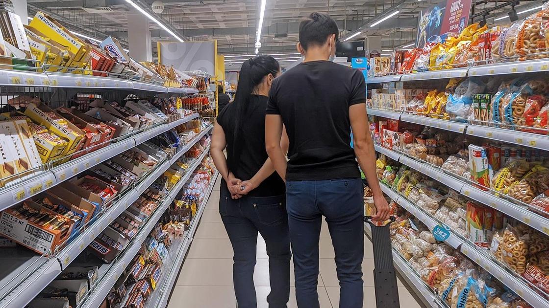 Парень и девушка выбирают продукты в супермаркете