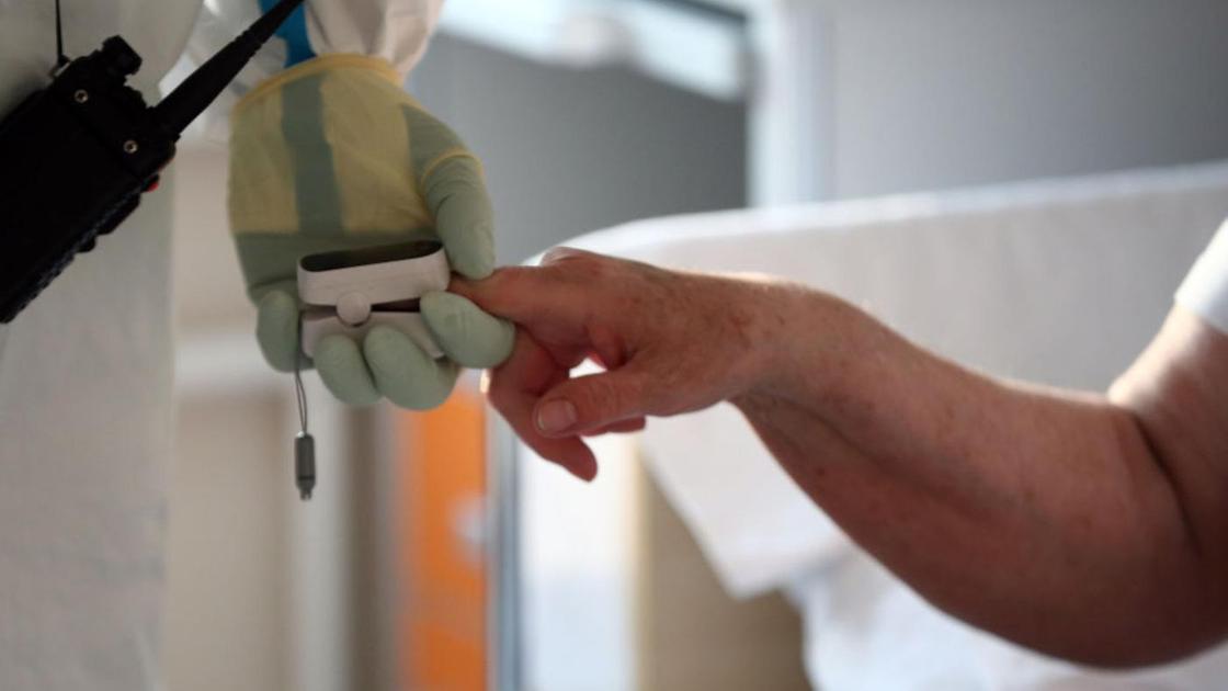 Медик дотрагивается до руки пациента