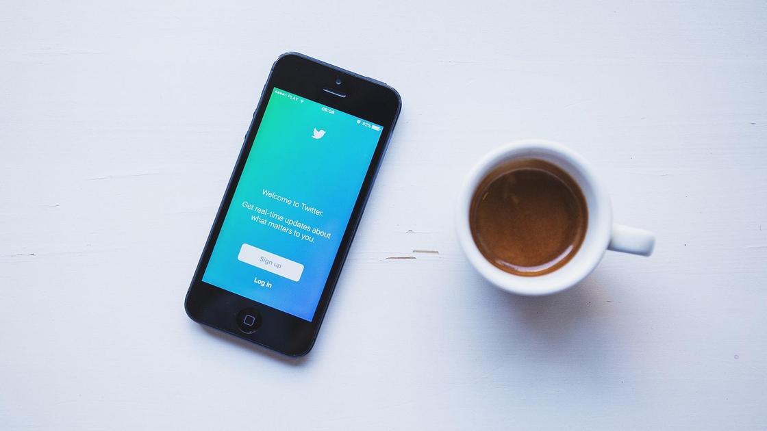 Смартфон и кружка с кофе на столе