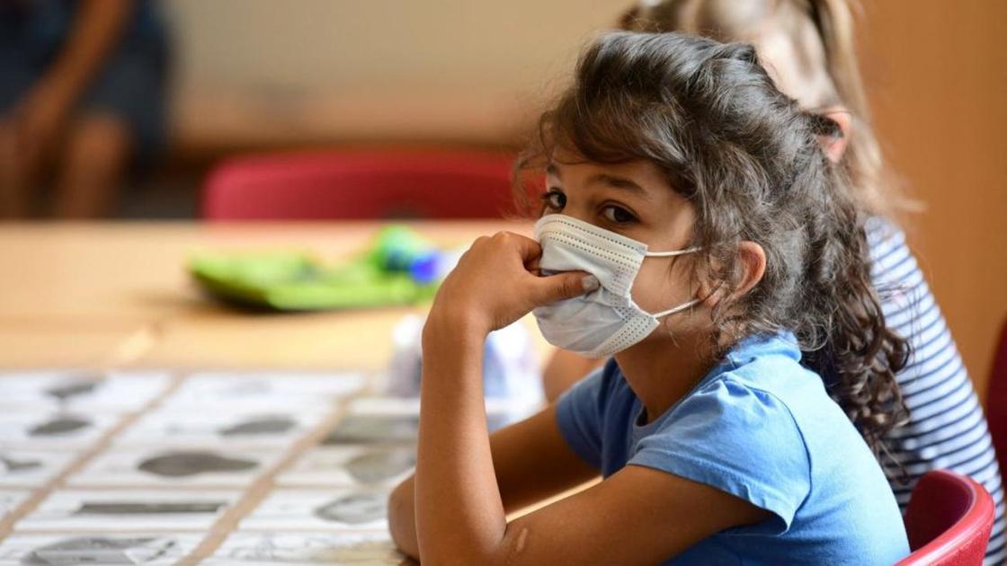 Девочка в медицинской маске сидит за столом