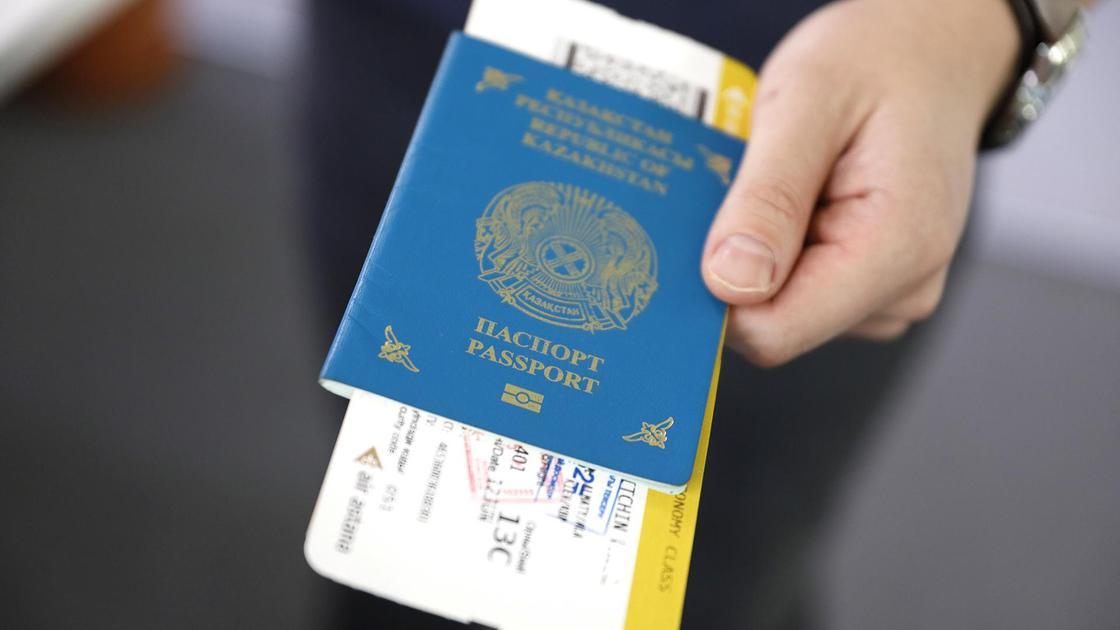 Мужчина держит паспорт с билетами на самолет