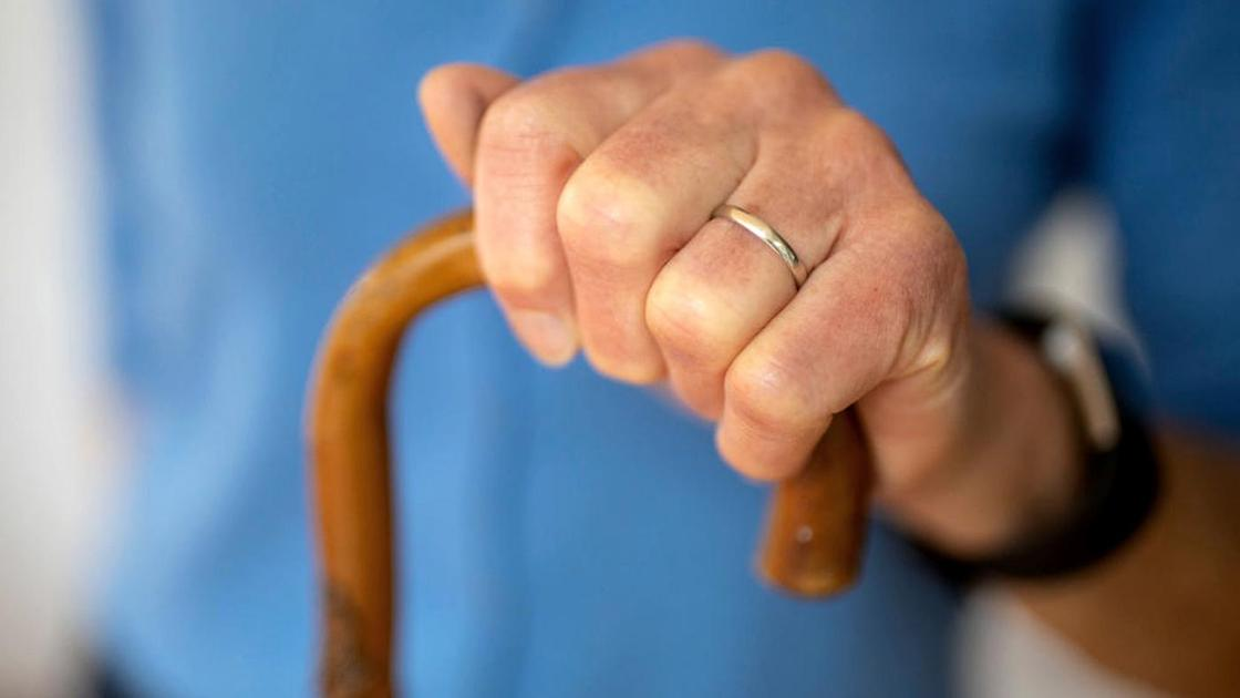Пожилая женщина держит рукой костыль