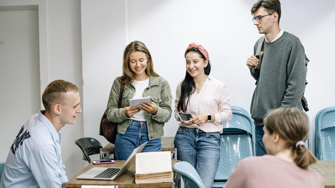 Студенты стоят в кабинете и улыбаются