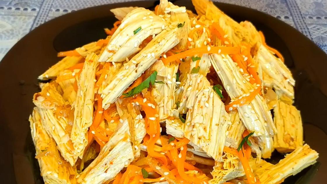 Салат из спаржи по-корейски с морковью на коричневой тарелке