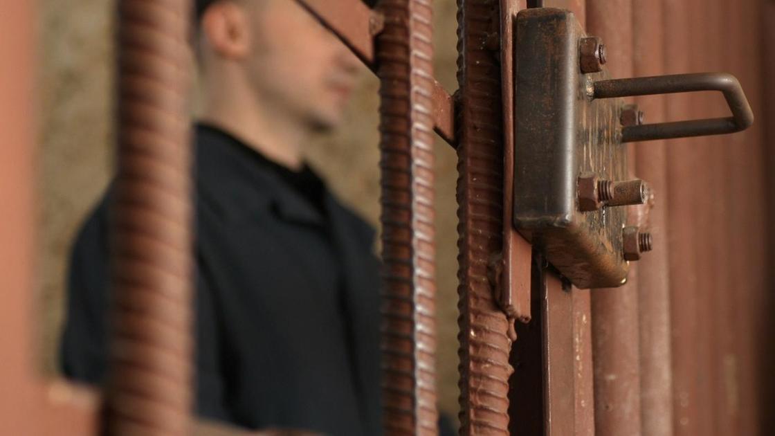 Мужчина за решеткой в зале суда
