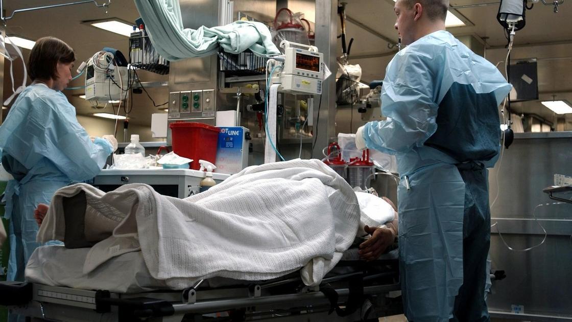 врачи стоят в палате рядом с больным