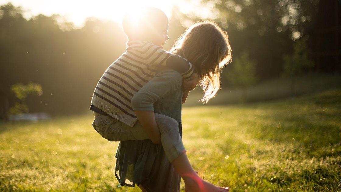 Девочка держит мальчика