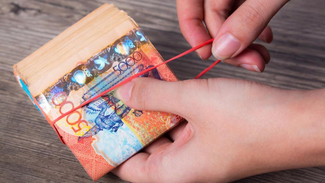 Женщина перетягивает пачку купюр тенге канцелярской резинкой