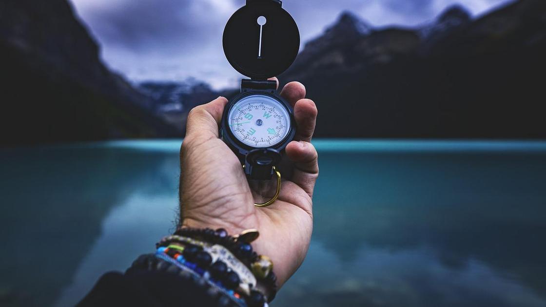 Мужчина держит в руке компас