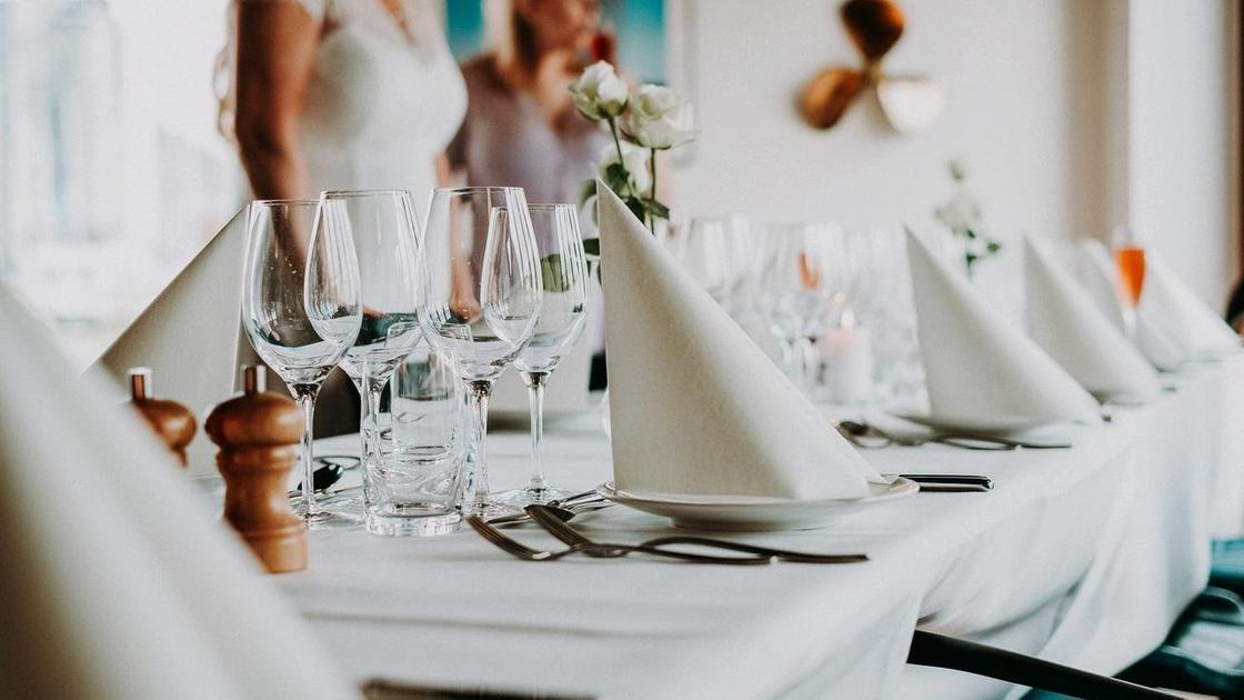 Бокалы и сложенные салфетки лежат на свадебном столе