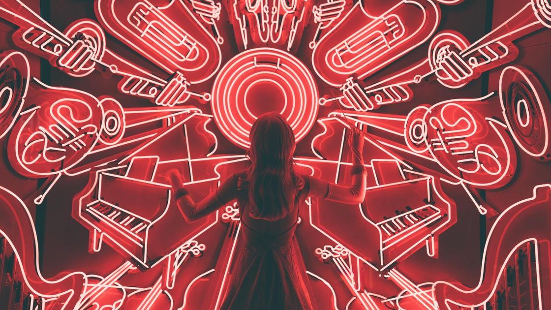 Девушка стоит перед неоновыми музыкальными инструментами