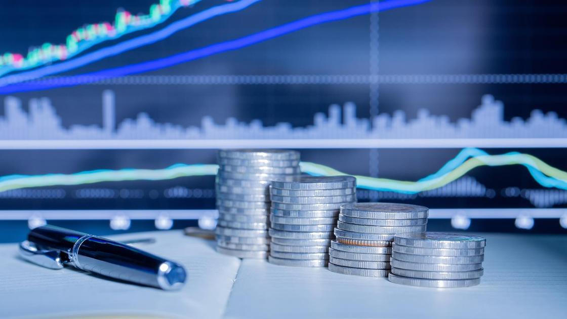 Монеты и ручки лежат на фоне графика