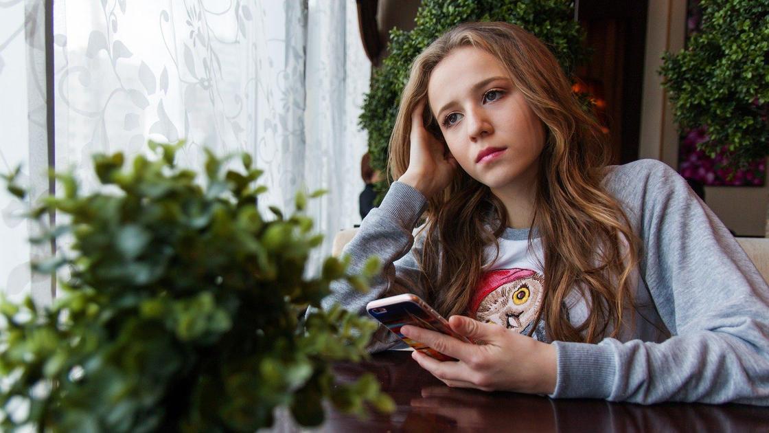 Печальная девушка сидит за столом