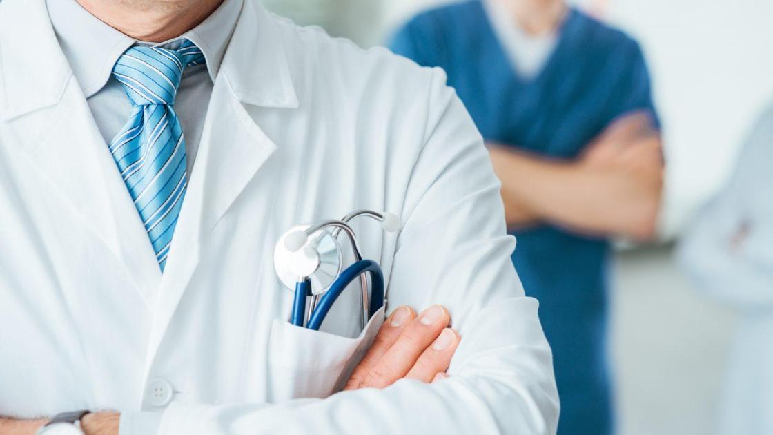 Медики в халатах стоят друг за другом