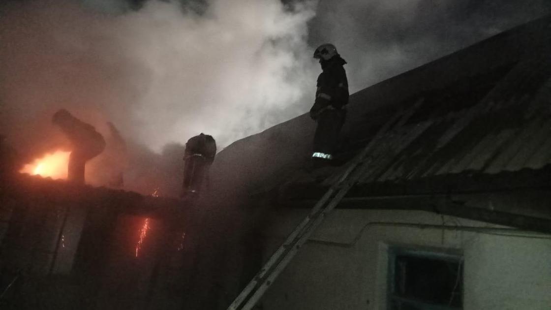 Пожарные на крыше горящего дома