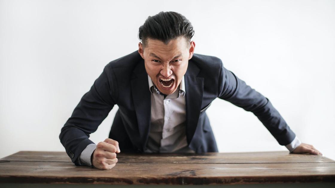 Мужчина в деловом костюме бьет рукой по столу и кричит