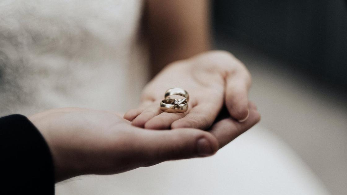 Пара держит в руках кольца