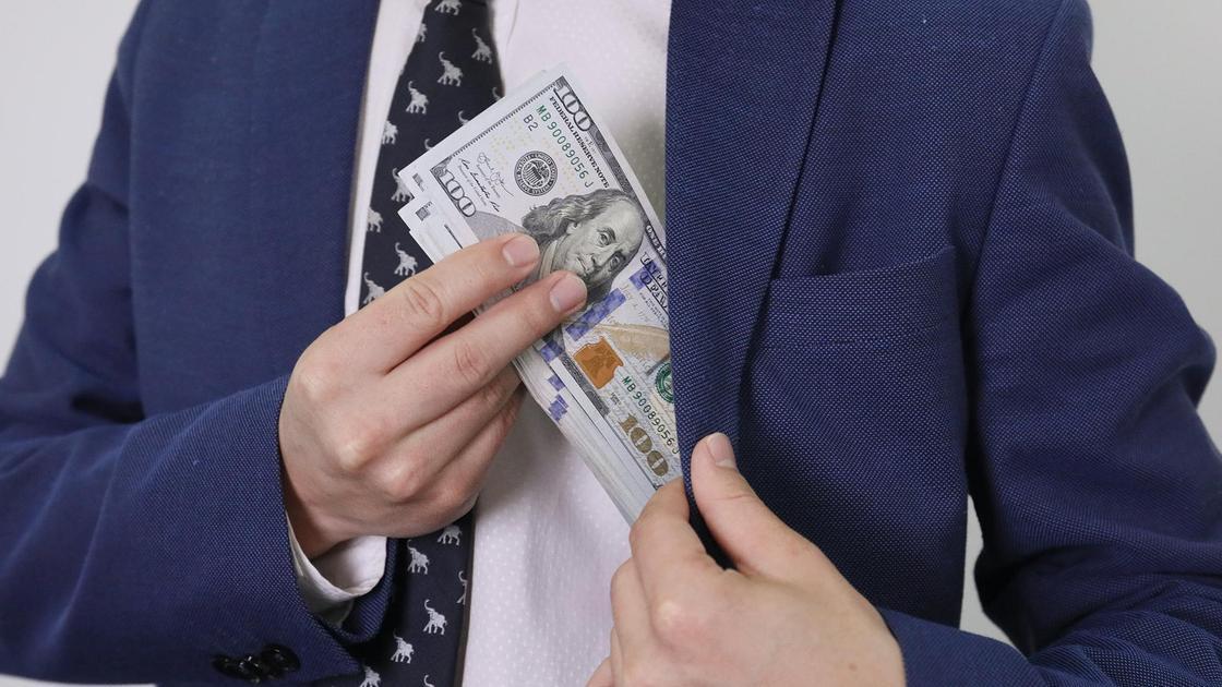 Мужчина кладет в карман пачку долларов