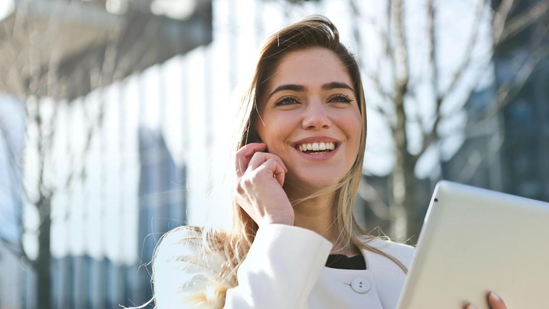 Девушка держит планшет и улыбается