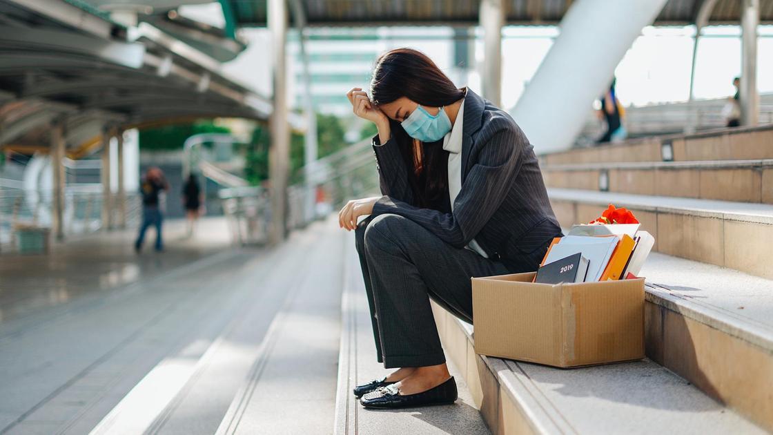 Женщина в маске сидит на лестнице с коробкой канцелярских принадлежностей