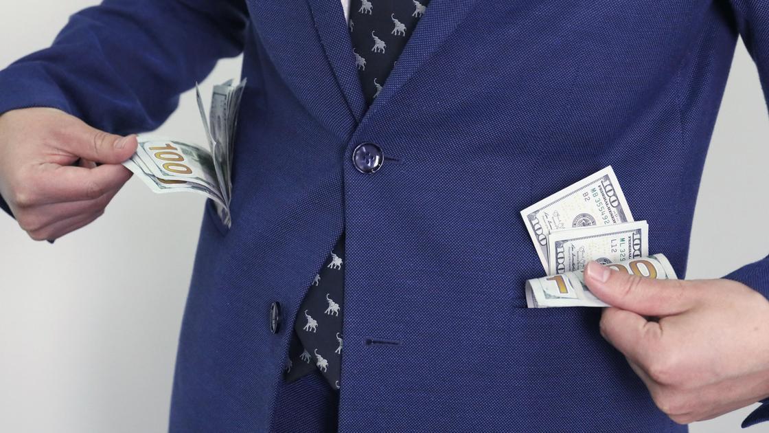 Карманы мужчины наполнены деньгами