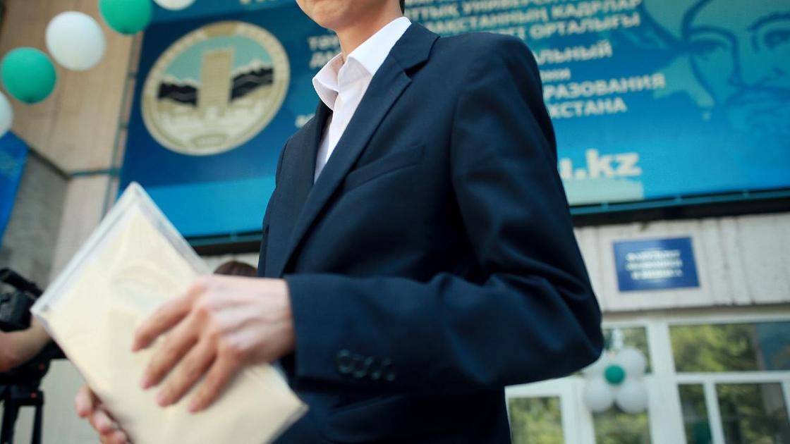 Школьник держит в руках тетрадь