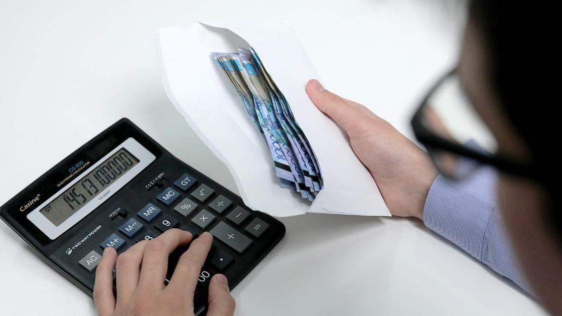 Мужчина держит в руке конверт с деньгами