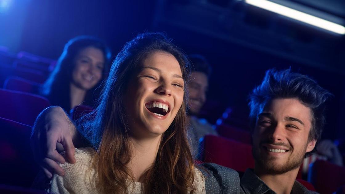 девушка с парнем смеются в кинозале