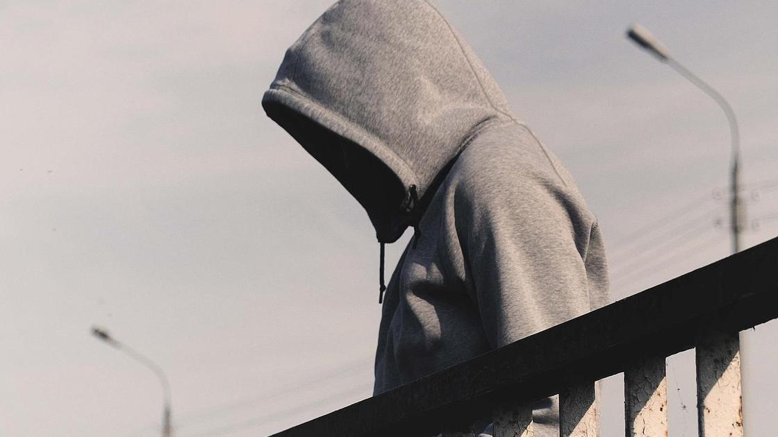 Мужчина в капюшоне стоит на мосту