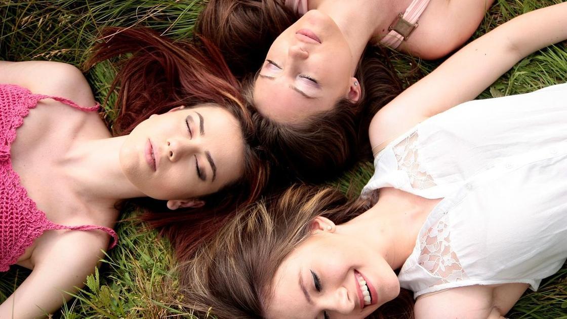 Девушки лежат на газоне