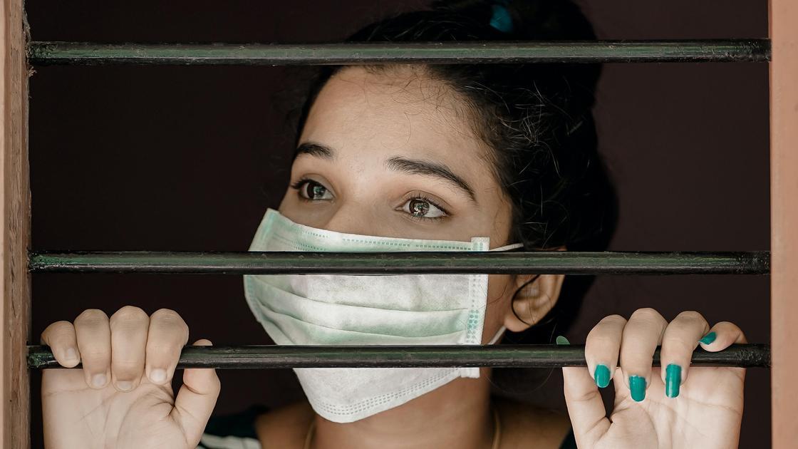 Девушка в маске за решеткой