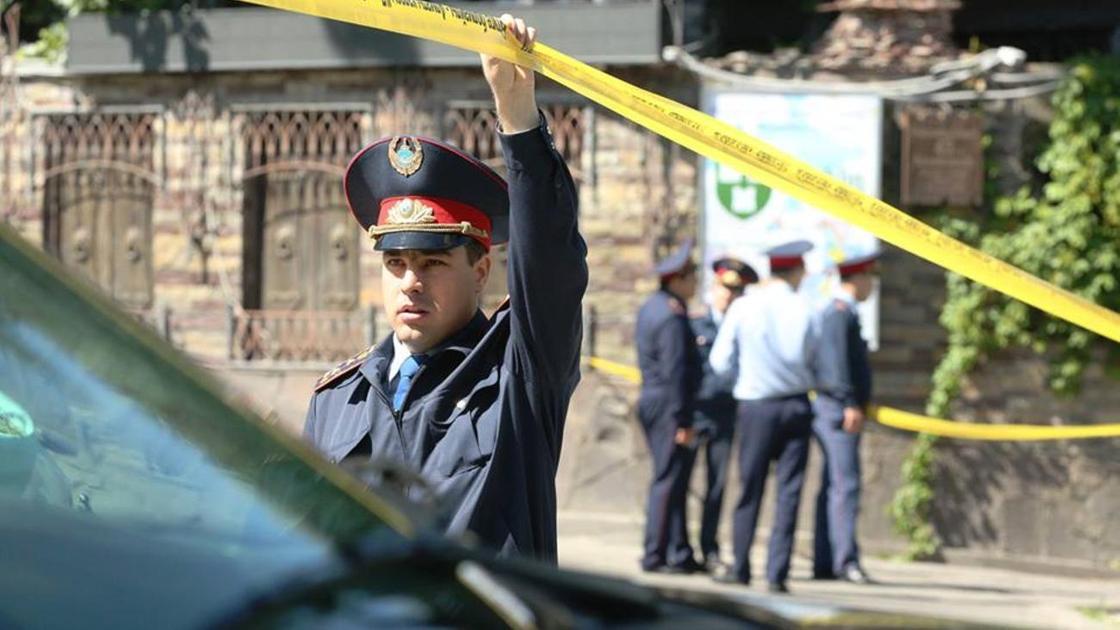 Полицейский проходит на территорию, огражденную желтой лентой